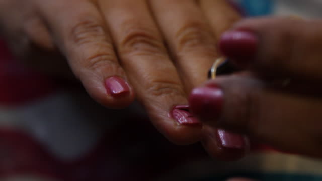 A woman paints her fingernails with pink polish