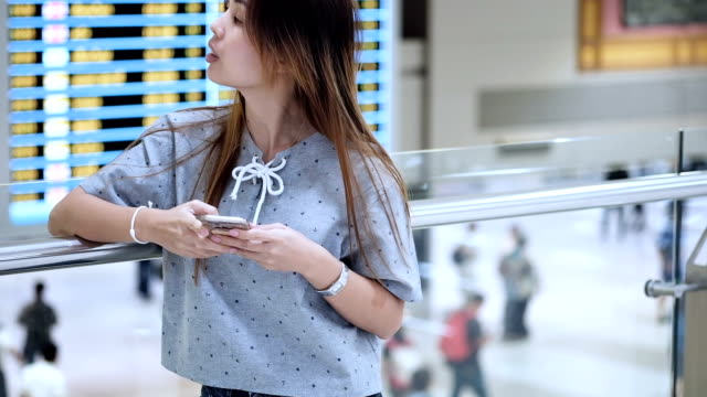 Woman passenger checking her flight on mobile phone
