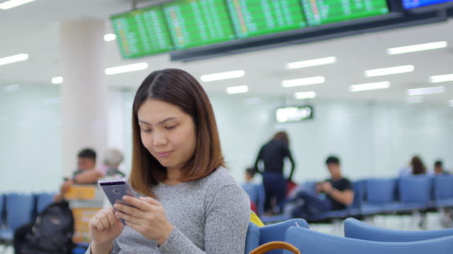Woman passenger touching and using smartphone waiting a flight at departure terminal airport