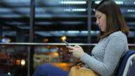 Woman passenger using mobile phone at departure terminal airport in night flight