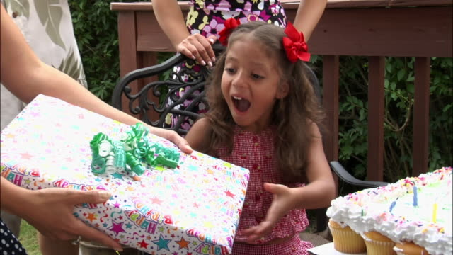 Woman passing girl gift at her birthday party / New Jersey
