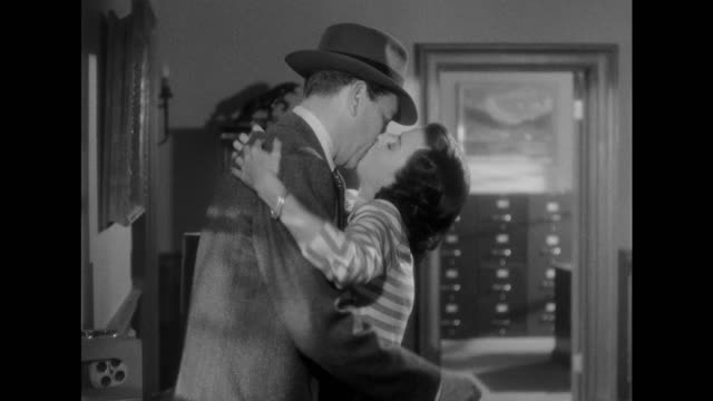 CU - Woman (Joan Bennett) passionately kisses man (Paul Henreid) mistaking him for his doctor lookalike