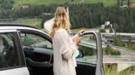 Woman pauses beside car door, checks phone for directions