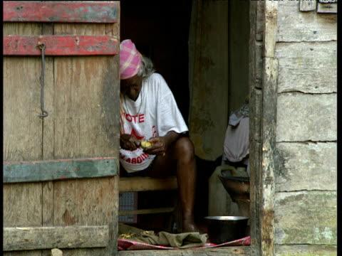 Woman peels banana sat in doorway of hut Windward Islands