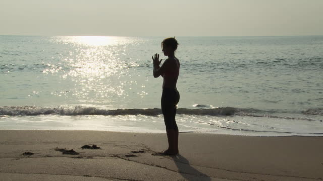 Woman performing sequence of yoga poses by the ocean