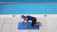 HA Woman performing yoga stretch at poolside,Mallorca