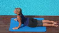 HA Woman performing yoga stretch at poolside,Mallorca
