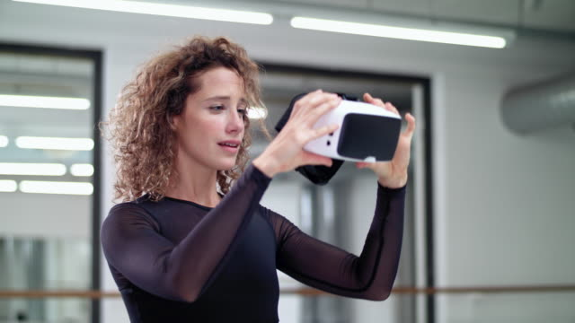 woman performs modern dance in a dance studio while using a VR headset (virtual reality)