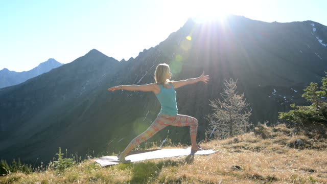 Woman performs yoga exercises in mountain meadow