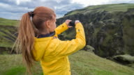 Woman photographing canyon