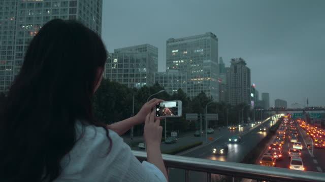 Woman photographing city night using phone