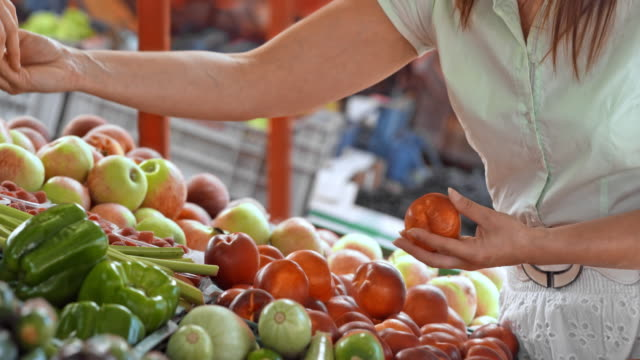 Woman picking out produce at a market stall and paying