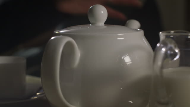 A woman picks up a white teapot at a tea room in the UK.