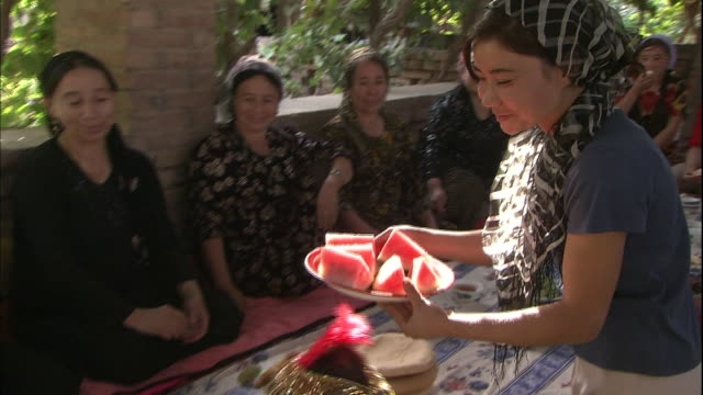 A woman places a plate of watermelon on a banquet table Silk Road China