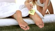 HD DOLLY: Woman Placing A Note On Boyfriend's Feet