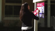 MS PAN Woman placing 'sold' sticker on real state sign outside house / Provo, Utah, USA