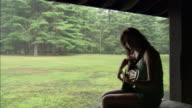 Woman playing guitar under shelter in park on rainy day / Connecticut