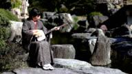 HD: Woman playing shamisen in Japanese garden (video)