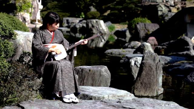 HD: Frau spielt shamisen in Japanischer Garten (video