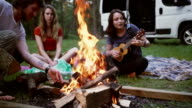 Woman playing ukulele near the campfire in forest