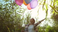 Woman playing with a bunch of balloons.