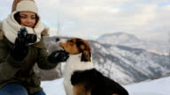 Woman playing with the dog in fresh snow