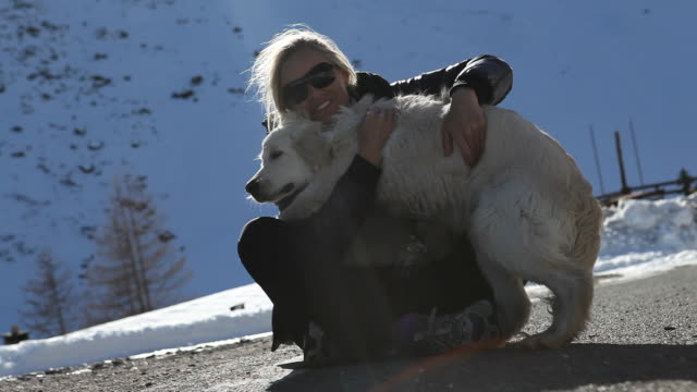 Woman plays with dog affectionately in mtn setting