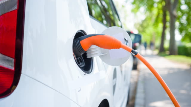 Woman plugging in electric car to charging station at an electric plug-in vehicle preferred parking in outskirts