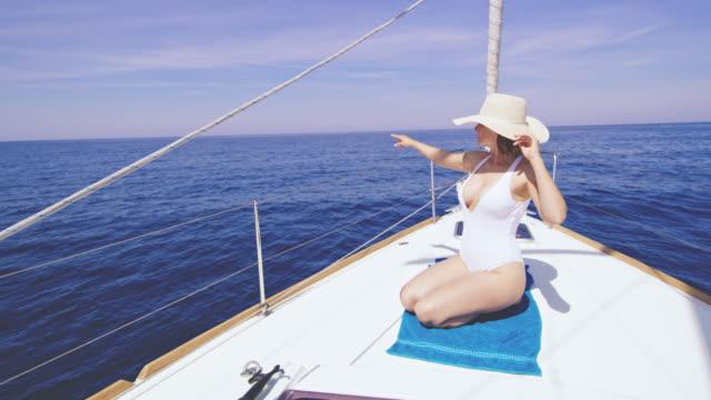 WS-Frau zeigt auf etwas und entspannen Sie an Deck eines Segelbootes