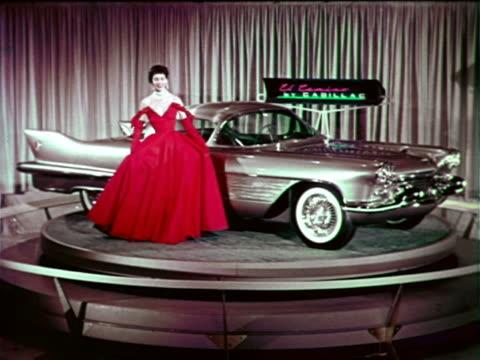 1954 woman posing by Cadillac El Camino on spinning platform at Motorama / industrial