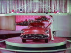 1954 woman posing by Oldsmobile Cutlass on spinning platform at Motorama / industrial