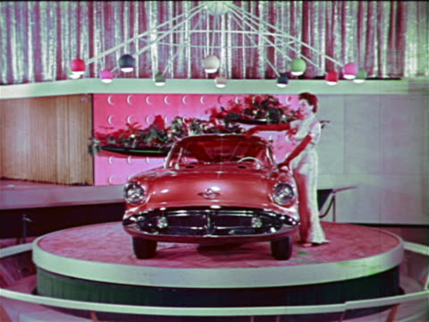 1954 woman posing by Oldsmobile Cutlass on spinning platform at Motorama / industrial