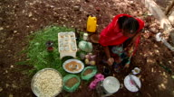 Woman pounding roasted coffee grains for coffee ceremony