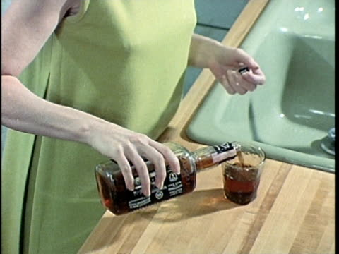 1971 MONTAGE Woman pouring and drinking alcohol in kitchen, Los Angeles, California, USA, AUDIO