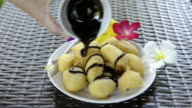 Woman pouring chocolate souce over fried banana