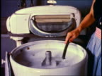1950 woman pouring soap into + operating old-fashioned electric washing machine
