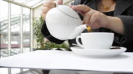 Woman pouring tea into cup in restaurant (HD720p)