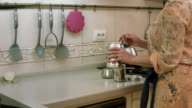 Woman pours coffe, sugar and water into cezve