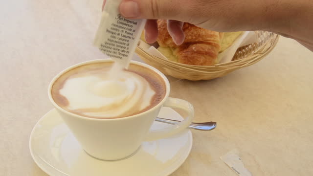 CU Woman pours sugar in cappuccino coffee and stirring with spoon and taking coffee cup to drink / Pietrasanta, Tuscany, Italy