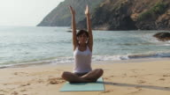 Woman practicing yoga by the ocean