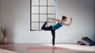 Woman practicing yoga in gym (lord of the dance pose)