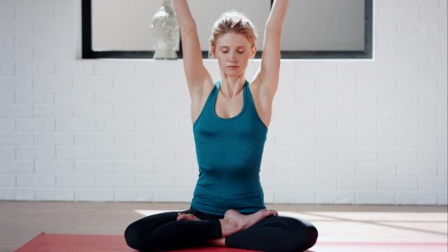 Woman practicing yoga in gym (lotus pose)