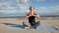MS Woman practicing yoga on beach / Rockaway, New Jersey,United States