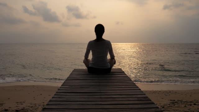 Kvinna tränar Yoga på träbron på stranden havet vid solnedgång, 4k(UHD)