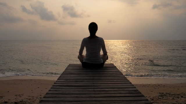 Frau üben Yoga auf dem hölzernen Brücke am Strand Meer während dem Sonnenuntergang 4 k (UHD