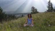 Woman practises yoga moves in mountain meadow