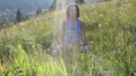 Woman practises yoga moves in mtn meadow, evening