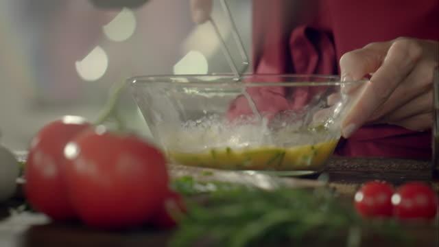 Woman preparing dressing for a salad