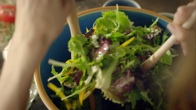 Woman preparing salad for dinner