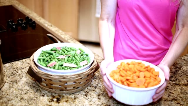 Woman preparing vegetables in home kitchen.